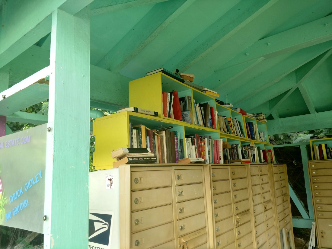 Books stacked on top of banks of metal mailboxes in a covered, outdoor area